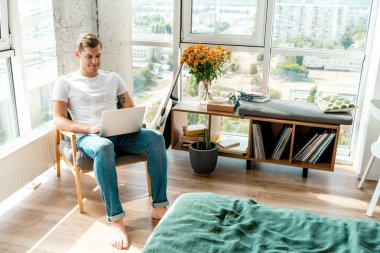 man in armchair using laptop at home
