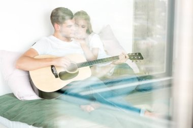 man playing acoustic guitar for girlfriend while resting on bed at home