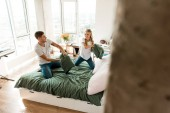 young couple in love having pillow fight on bed at home