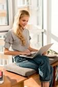 usměvavá mladá žena přenosném počítači při sezení u okna doma