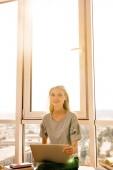 Porträt der jungen Frau mit Laptop Fenster zu Hause sitzen