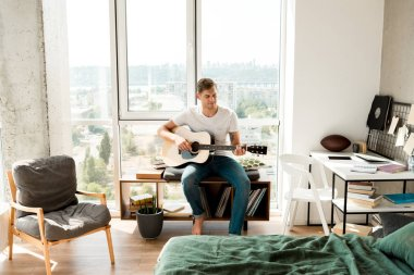 young man in casual clothing playing acoustic guitar at home