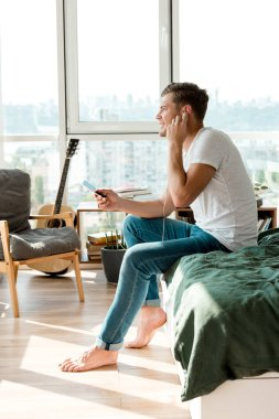 side view of man in earphones listening music at home