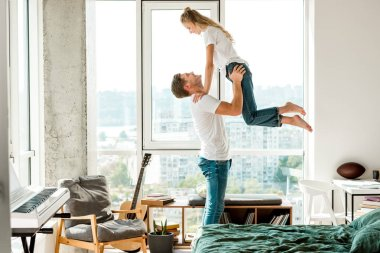side view of cheerful man holding girlfriend in hands while standing at window at home