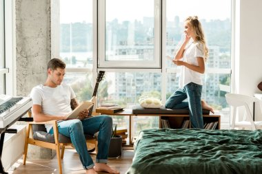 young woman in earphones listening music while boyfriend reading book in armchair at home