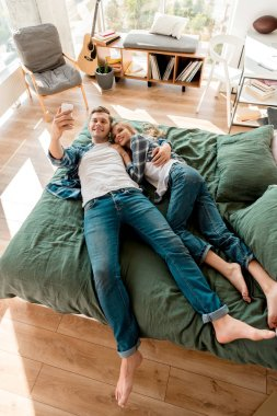 high angle view of cheerful young couple taking selfie on smartphone while lying on bed at home