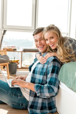 Happy couple with digital laptop at home stock vector