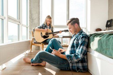 focused man using digital tablet while girlfriend playing acoustic guitar at home