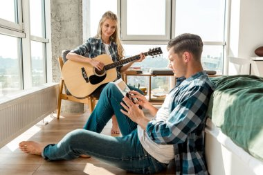 man using digital tablet while girlfriend playing acoustic guitar at home