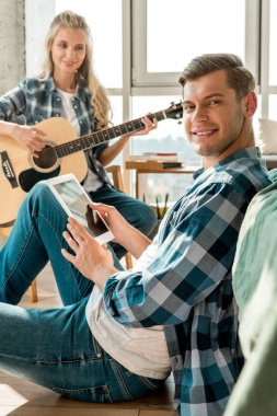 smiling man with digital tablet and girlfriend with acoustic guitar at home