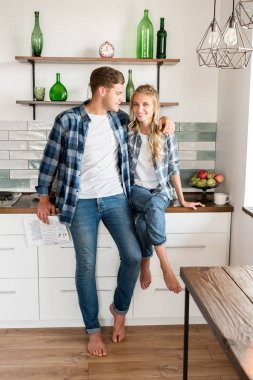smiling loving couple in casual clothing in kitchen at home