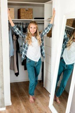 smiling woman standing at wardrobe at home