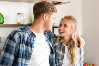 portrait of happy loving couple in casual clothing in kitchen at home