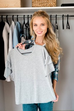 young smiling woman fitting grey tshirt at home