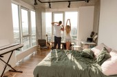 Fotografie Rückansicht des jungen Paares im Pyjama stretching am Fenster zu Hause Morgen