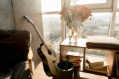 Fotografie close up view of acoustic guitar and beautiful bouquet of flowers at window