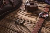 Chiuda sulla vista di accessori maschili in pelle e scarpe disposte su piano in legno