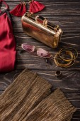 Fotografie close up view of fashionable red and golden female purse, sunglasses and jewelry on wooden tabletop