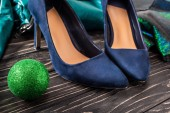 Fotografie close up view of bright feminine blue shoes and green chirstmas ball on wooden surface