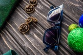 Fotografie close up view of stylish sunglasses and earrings on wooden tabletop
