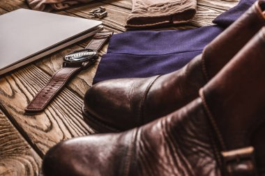 close up view of laptop, leather male shoes and clothing on wooden tabletop