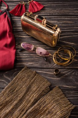 close up view of fashionable red and golden female purse, sunglasses and jewelry on wooden tabletop