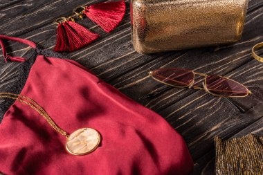 close up view of red and golden feminine accessories on wooden surface