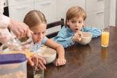 Fotografie Schuss von Mutter gießt Orangensaft für entzückende kleine Kinder beschnitten, während des Frühstücks