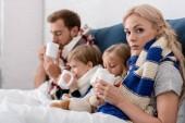 Kranke junge Familie trinkt wärmende Getränke im Bett