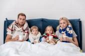 Fotografia malato giovane famiglia con tazze di bevanda calda seduta nel letto e rivolto verso lobiettivo