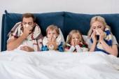 beteg fiatal család fúj szalvéták, orrok együtt, miközben az ágyban fekve