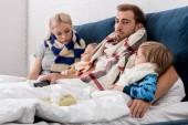 Kranke junge Familie in Schals mit Fernbedienung im Bett liegend