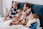 Fotografie nemocný mladá rodina v šátky na sebe dívali, když ležíte v posteli
