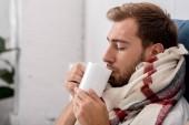 Fotografia Ritratto del primo piano del malato giovane in sciarpa con la tazza di tè