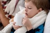 Fotografia Ritratto del primo piano di piccolo bambino in sciarpa con tazza di bevanda calda che si siede nel letto