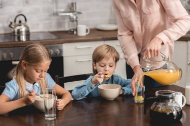 cropped shot of mother pouring orange juice for kids during breakfast