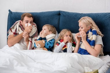 sick young family blowing noses with napkins together while lying in bed and looking at each other