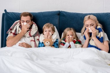 sick young family blowing noses with napkins together while lying in bed