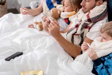 cropped shot of sick young family looking at electric thermometers while lying in bed