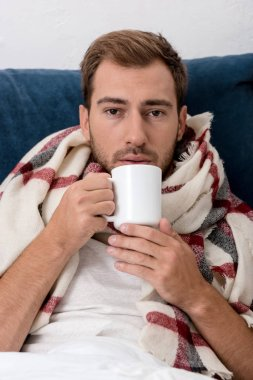 Close-up portrait of sick young man in scarf with cup of tea looking at camera stock vector