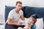Fotografie otec, kontrola teploty syna s elektrickým teploměrem a drží ledový obklad na hlavu v posteli a při pohledu na fotoaparát