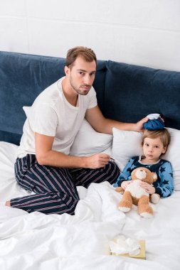 high angle view of father checking temperature of son with electric thermometer and holding ice pack on his head in bed and looking at camera