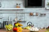 Fotografie zblízka střílel ze syrové zeleniny na stůl v moderní kuchyni