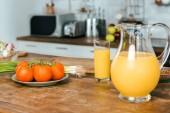 Fotografie zblízka střílel syrová rajčata s pórkem a džbánek pomerančového džusu na stůl v moderní kuchyni