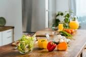 Fotografie zblízka střílel z různých syrovou zeleninu na stůl v moderní kuchyni
