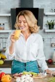 krásná pro dospělé žena pít pomerančový džus při vaření v kuchyni