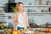 Fotografie usměvavá mladá žena s pórkem, při vaření v kuchyni při pohledu na fotoaparát