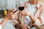 cropped shot of women clinking with glasses of red wine