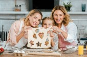 Photo happy child with mother and grandmother holding cutted dough with heart, star and christmas tree shaped holes at home