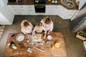 Fényképek a gyermek az anya és a nagymama vágás tészta karácsonyi sütik otthon felülnézet